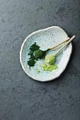 Bio-Chlorella und Gerstengras-Pulver auf Keramiklöffeln