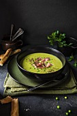 A bowl of pea and ham soup with bread and parsley