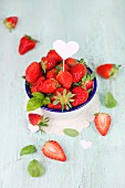 Fresh strawberries and a heart stick with basil