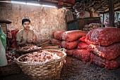 A woman peeling onions at Hsipaw market (Myanmar, Burma)
