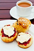 Scones with strawberry jam and clotted cream served with tea (England)