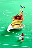 Pancakes with dried tomatoes and salami with a football decorations