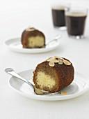 Zwei Stücke Kaffee-Rum-Kuchen mit Mandeln auf Tellern