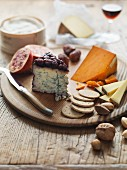 A cheese platter with crackers, nuts and fruit