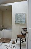 Blick auf Holzstuhl, im Hintergrund Badewanne teilweise sichtbar, schlichtes Bad mit Dielenboden, weiße abblätternde Farbe