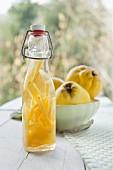 Ansatz für Quittenschnaps in Flasche, dahinter frische Quitten in einer Vintage-Schale