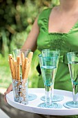A woman serving breadsticks and sparkling wine