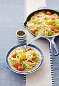 Spaghetti with yellow and red tomatoes, garlic and basil
