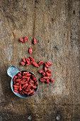 Dried goji berries in small bowls on a wooden background (top view)