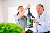 Mann und Frau beim Zubereiten eines Gemüsesmoothies in der Küche