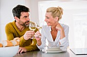 A middle-aged couple sitting in the kitchen toasting with glasses of wine