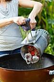 Frau schüttet glühende Grillkohle aus dem Anzünder in Kugelgrill