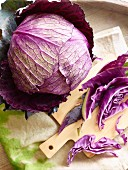 A fresh red cabbage, partially sliced
