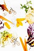 Stillleben mit Obst- und Gemüsescheiben, Salat und Saucen