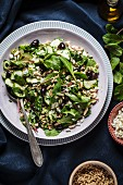 Spinach salad with pine nuts, olives and cucumber