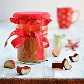 A jar of homemade rhubarb compote with a red bow
