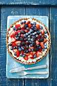 Berry tart with chocolate cream, strawberry jam, whipped cream and fresh berries