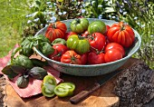 Red and green tomatoes with basil in a bowl on a tree stump