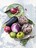 Artichokes, aubergines, green tomatoes, onions and garlic on a wooden table