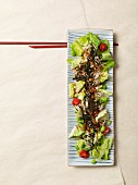 A mixed leaf salad with soba noodles, cos lettuce and edamame beans