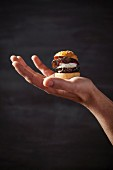 A mini veggie burger on a hand