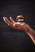 Vegetarischer Mini-Burger auf Hand