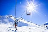 Skiers ascending on a ski lift
