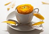 Gelbe Ranunkel in weisser Espressotasse