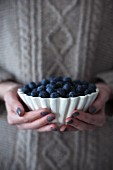 A woman holding a bowl of fresh blueberries