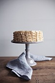 A cream cake with peanut butter cream on a cake stand