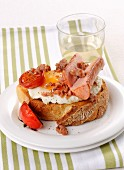 Crostoni top with fried egg, sausage and cherry tomatoes