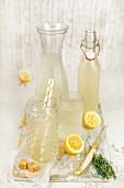 Thymian-Zitronenlimonade in Flasche, Karaffe und Gläsern