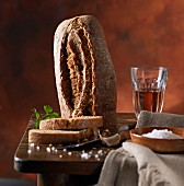 A rustic loaf of bread with coarse salt and wine on a wooden table