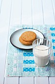 Glass of milk and plate of biscuits on place mat hand-made from woven strips of pastel fabrics