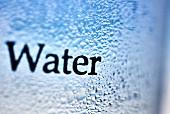 Beschlagenes Wasserglas mit Schriftzug (Close Up)