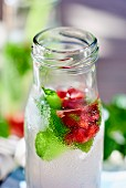 A bottle of lemon juice with pomegranate seeds and mint