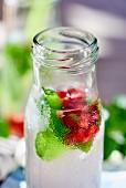 Zitronensaft mit Granatapfelkernen und Minze in Flasche