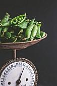 Frische Erbsen auf alter Küchenwaage
