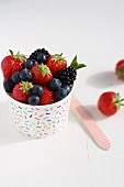 Various berries in a colourful tub