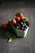 Various berries with mint in an old-fashioned cardboard punnet