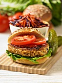 A veggie burger with chilli sauce, tomatoes and lettuce