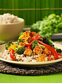 Sweet-and-sour fried tofu with pepper and broccoli on a bed of rice