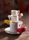 Tee in gestreiften Tassen und Macarons