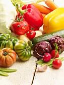Gemüsestillleben mit Sommergemüse und Tomatengesicht