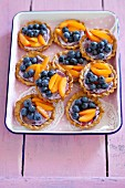 Mini tartlets with blueberry mascarpone cream, fruit and honey