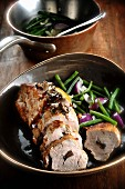Stuffed roast pork with onions and beans