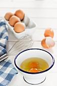 Aufgeschlagene Eier in Emailleschüssel und ganze Eier im Eierkarton