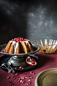Pomegranate and rosewater cake with icing on a metal cake stand