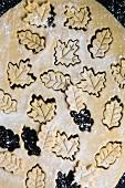 Plätzchenteig mit ausgestochenen blattförmigen Keksen