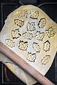 Ausgerollter Plätzchenteig mit ausgestochenen blattförmigen Keksen